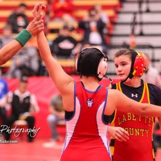 An Official holds up the hand of Mariyah Reyes (Dodge City) in victory over Abbie Jones (Altamont-Labette County). The first ever Kansas High School Girls Wrestling Championship was held at the Roundhouse at McPherson High School in McPherson, Kansas on February 11, 2017. (Photo: Joey Bahr, www.joeybahr.com)