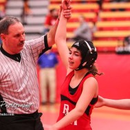 An official holds up the arm of Anayka Besco (Rose Hill) for her 11-3 major decision over Amanda Newcomb (Osawatomie) to take the weight class 106 State Championship. The first ever Kansas High School Girls Wrestling Championship was held at the Roundhouse at McPherson High School in McPherson, Kansas on February 11, 2017. (Photo: Joey Bahr, www.joeybahr.com)