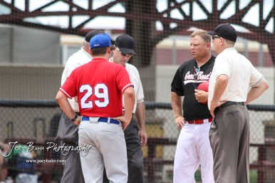 Hays Eagle Head Coach Dustin Schumacher (#29) and Great Bend Chief Head Coach Mike Perry (#26) meet with the Umpire crew prior to the start of the game. The Great Bend American Legion Post 180 AAA Cheifs defeated the Hays American Legion Post 173 AAA Eagles 3 to 1 to advance to the AAA Zone 8 Championship at the Great Bend Sports Complex in Great Bend, Kansas on July 15, 2017. (Photo: Joey Bahr, www.joeybahr.com)