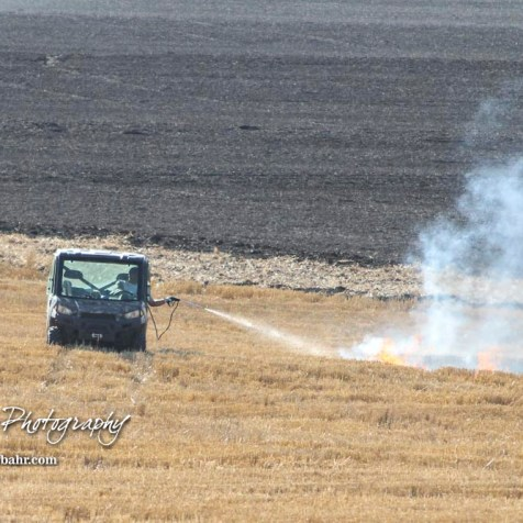 Corey Wagner uses a sprayer try and stop the progress of the fire in a wheat stubble field. Members of the Olmitz, Hoisington, and Galatia Fire Departments respond to a controlled burn that got out of control two miles north of the junction of Kansas Highway 4 and US Highway 281 near Hoisington, Kansas on July 1, 2017. (Photo: Joey Bahr, www.joeybahr.com)