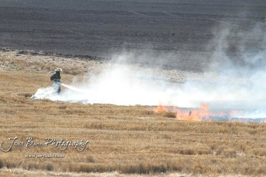 A firefighter uses a hose dismounted from a truck to extinguish flames in the wheat stubble field. Members of the Olmitz, Hoisington, and Galatia Fire Departments respond to a controlled burn that got out of control two miles north of the junction of Kansas Highway 4 and US Highway 281 near Hoisington, Kansas on July 1, 2017. (Photo: Joey Bahr, www.joeybahr.com)