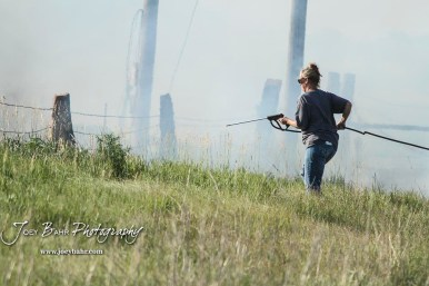 Jatim Wagner drags a spray nozzle and hose to try and stop the fire from spreading in the ditch on the side of US Highway 281. Members of the Olmitz, Hoisington, and Galatia Fire Departments respond to a controlled burn that got out of control two miles north of the junction of Kansas Highway 4 and US Highway 281 near Hoisington, Kansas on July 1, 2017. (Photo: Joey Bahr, www.joeybahr.com)