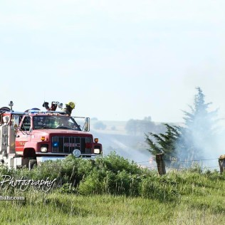 A truck from the Hoisington Fire Department sprays down hotspots near the end of field. Members of the Olmitz, Hoisington, and Galatia Fire Departments respond to a controlled burn that got out of control two miles north of the junction of Kansas Highway 4 and US Highway 281 near Hoisington, Kansas on July 1, 2017. (Photo: Joey Bahr, www.joeybahr.com)
