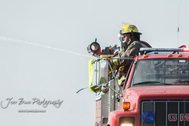 A firefighter with the Hoisington Fire Department aims his hose higher to extinguish some flames. Members of the Olmitz, Hoisington, and Galatia Fire Departments respond to a controlled burn that got out of control two miles north of the junction of Kansas Highway 4 and US Highway 281 near Hoisington, Kansas on July 1, 2017. (Photo: Joey Bahr, www.joeybahr.com)