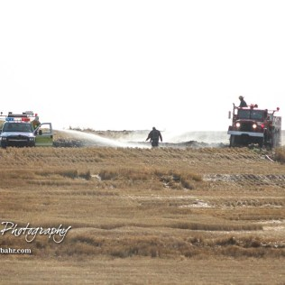 Trucks from Galatia and Hoisington along with a firefighter work to extinguish a hotspot in the field. Members of the Olmitz, Hoisington, and Galatia Fire Departments respond to a controlled burn that got out of control two miles north of the junction of Kansas Highway 4 and US Highway 281 near Hoisington, Kansas on July 1, 2017. (Photo: Joey Bahr, www.joeybahr.com)
