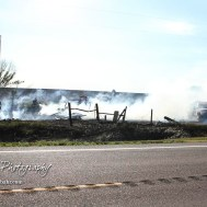 Multiple fire units converge on a burning wood pile in the corner of the property. Members of the Olmitz, Hoisington, and Galatia Fire Departments respond to a controlled burn that got out of control two miles north of the junction of Kansas Highway 4 and US Highway 281 near Hoisington, Kansas on July 1, 2017. (Photo: Joey Bahr, www.joeybahr.com)