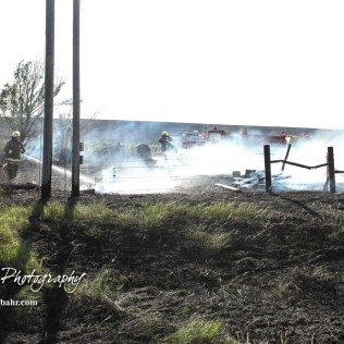 A dismounted firefighter turns his hose on a burning wood pile in the corner of the property. Members of the Olmitz, Hoisington, and Galatia Fire Departments respond to a controlled burn that got out of control two miles north of the junction of Kansas Highway 4 and US Highway 281 near Hoisington, Kansas on July 1, 2017. (Photo: Joey Bahr, www.joeybahr.com)