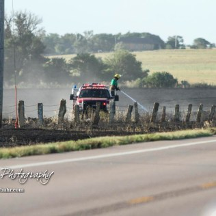 A Hoisington firefighter uses a hose on a possible hotspot along the fence row. Members of the Olmitz, Hoisington, and Galatia Fire Departments respond to a controlled burn that got out of control two miles north of the junction of Kansas Highway 4 and US Highway 281 near Hoisington, Kansas on July 1, 2017. (Photo: Joey Bahr, www.joeybahr.com)