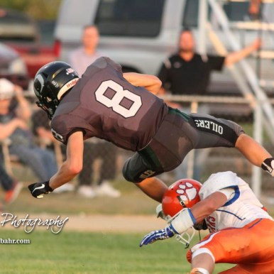 Central Plains Oiler #8 Anthony Oberle flies over Otis-Bison Cougar #8 Daniel Scott to score a touchdown in the second quarter. The Central Plains Oilers defeated the Otis-Bison Cougars by a score of 36 to 12 at Central Plains High School in Claflin, Kansas on September 15, 2017. (Photo: Joey Bahr, www.joeybahr.com)