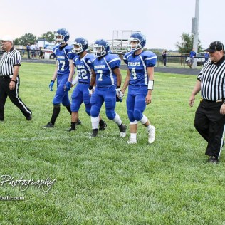 The St. John Tiger team captains walk out on to the field for the coin toss. The Otis-Bison Cougars defeated the St. John Tigers by a score of 58 to 0 at St. John High School in St. John, Kansas on September 1, 2017. (Photo: Joey Bahr, www.joeybahr.com)