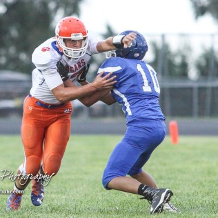 Otis-Bison Cougar #17 Anton Foust muscles through the block of St. John Tiger #10 Eddy Calleros in the first quarter. The Otis-Bison Cougars defeated the St. John Tigers by a score of 58 to 0 at St. John High School in St. John, Kansas on September 1, 2017. (Photo: Joey Bahr, www.joeybahr.com)