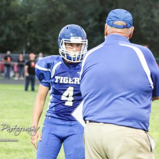 St. John Tiger Head Coach Mike Joiner tells #4 Cashe McVay the next play in the second quarter. The Otis-Bison Cougars defeated the St. John Tigers by a score of 58 to 0 at St. John High School in St. John, Kansas on September 1, 2017. (Photo: Joey Bahr, www.joeybahr.com)