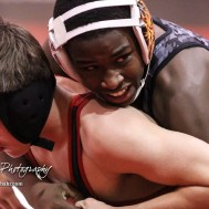 Samajay Alboyd of Larned looks to his coaches for guidance as he grapples with Skylar Burkes of Great Bend in a 126 pound weight class match. Burkes won the match in a 8 to 6 decision. The 2017 Cardinal Corner Classic Wrestling Tournament was held at Hoisington Activity Center in Hoisington, Kansas on December 15, 2017. (Photo: Joey Bahr, www.joeybahr.com)