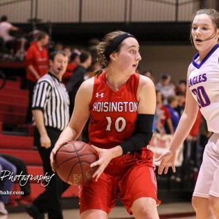 Hoisington Lady Cardinal #10 Brooke Reif looks for a teammate to pass the ball to as Ellinwood Lady Eagle #30 Rebecca Henderson defends. The Hoisington Lady Cardinals defeated the Ellinwood Lady Eagles by a score of 46 to 19 in the Consolation Semi-Final of the 2018 Hoisington Winter Jam at the Hoisington Activity Center in Hoisington, Kansas on January 18, 2018. (Photo: Joey Bahr, www.joeybahr.com)