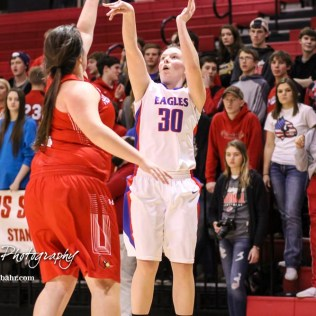 Hoisington Lady Cardinal #5 Jocelynn Pedigo tries to get a hand on a shot by Ellinwood Lady Eagle #30 Rebecca Henderson. The Hoisington Lady Cardinals defeated the Ellinwood Lady Eagles by a score of 46 to 19 in the Consolation Semi-Final of the 2018 Hoisington Winter Jam at the Hoisington Activity Center in Hoisington, Kansas on January 18, 2018. (Photo: Joey Bahr, www.joeybahr.com)