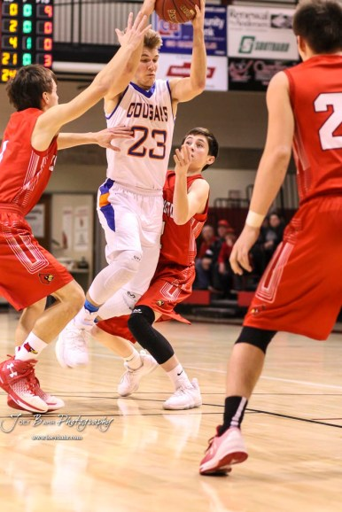Otis-Bison Cougar #23 Maitland Wiltse splits the defense of Hoisington Cardinals #4 Mason Haxton and #2 Avery Brewer. The Hoisington Cardinals defeated the Otis-Bison Cougars by a score of 58 to 46 in the Semi-Final of the 2018 Hoisington Winter Jam at the Hoisington Activity Center in Hoisington, Kansas on January 19, 2018. (Photo: Joey Bahr, www.joeybahr.com)