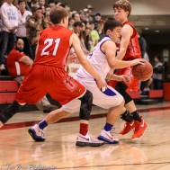 Otis-Bison Cougar #14 Seth Hoopingarner dribbles between Hoisington Cardinals #21 Isaac Prosser and #5 Ryan Woydziak. The Hoisington Cardinals defeated the Otis-Bison Cougars by a score of 58 to 46 in the Semi-Final of the 2018 Hoisington Winter Jam at the Hoisington Activity Center in Hoisington, Kansas on January 19, 2018. (Photo: Joey Bahr, www.joeybahr.com)