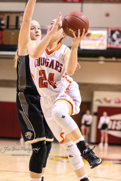 Otis-Bison Lady Cougar #24 Cristen Trapp goes for a layup as LaCrosse Lady Leopard #25 Addie Kershner defends. The Otis-Bison Lady Cougars defeated the LaCrosse Lady Leopards by a score of 29 to 23 in the Semi-Final of the 2018 Hoisington Winter Jam at the Hoisington Activity Center in Hoisington, Kansas on January 19, 2018. (Photo: Joey Bahr, www.joeybahr.com)