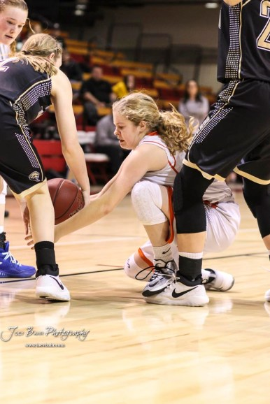 Otis-Bison Lady Cougar #14 Ashtyn Butler tries to pull in a loose ball. The Otis-Bison Lady Cougars defeated the LaCrosse Lady Leopards by a score of 29 to 23 in the Semi-Final of the 2018 Hoisington Winter Jam at the Hoisington Activity Center in Hoisington, Kansas on January 19, 2018. (Photo: Joey Bahr, www.joeybahr.com)