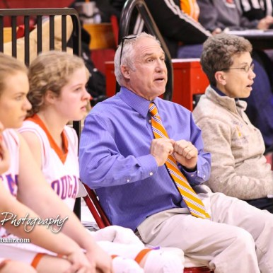Otis-Bison Lady Cougar Head Coach Stan Ewy displays a playing technique from the bench. The Otis-Bison Lady Cougars defeated the LaCrosse Lady Leopards by a score of 29 to 23 in the Semi-Final of the 2018 Hoisington Winter Jam at the Hoisington Activity Center in Hoisington, Kansas on January 19, 2018. (Photo: Joey Bahr, www.joeybahr.com)