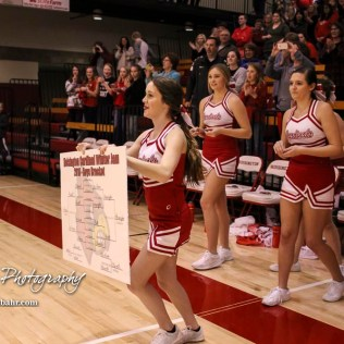 A Hoisington Cheerleader brings out a copy of the completed tournament bracket to the victors. The Hoisington Cardinals defeated the Pratt Greenbacks by a score of 47 to 41 in the Boys Championship game of the 2018 Hoisington Winter Jam at the Hoisington Activity Center in Hoisington, Kansas on January 20, 2018. (Photo: Joey Bahr, www.joeybahr.com)