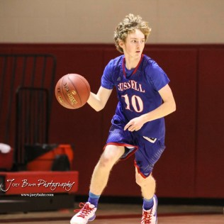 Russell Bronco #10 Koby Decker looks for an open teammate to pass the ball to. The Russell Broncos defeated the Ellinwood Eagles by a score of 60 to 17 in the Consolation Semi-Final of the 2018 Hoisington Winter Jam at the Hoisington Activity Center in Hoisington, Kansas on January 18, 2018. (Photo: Joey Bahr, www.joeybahr.com)
