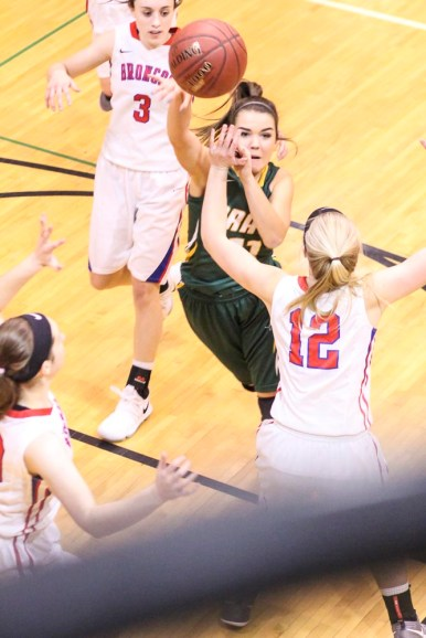 Pratt Lady Greenback #11 Danielle Staats passes the ball to a teammate as Russell Lady Bronco #12 Janae Schulte defends. The Russell Lady Broncos faced the Pratt Lady Greenbacks in the First Round of the 2018 Hoisington Winter Jam at the Hoisington High School in Hoisington, Kansas on January 16, 2018. (Photo: Joey Bahr, www.joeybahr.com)