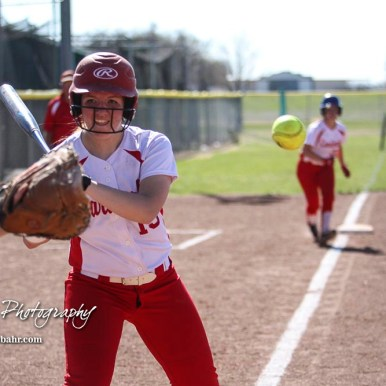 Hoisington Lady Cardinal Brooke Steinert (#15) watches a pitch head towards the catcher's glove in the bottom of the third inning. The Hoisington Lady Cardinals defeated the Halstead Lady Dragons by a score of 12 to 2 in six innings at Logan Field in Hoisington, Kansas on April 27, 2018. (Photo: Joey Bahr, www.joeybahr.com)