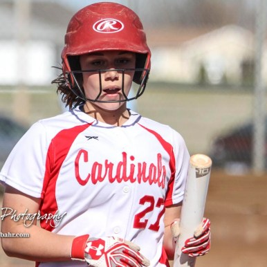 Hoisington Lady Cardinal Jenna Urban (#27) brings a bat back to the dugout after scoring a run in the bottom of the fifth inning. The Hoisington Lady Cardinals defeated the Halstead Lady Dragons by a score of 12 to 2 in six innings at Logan Field in Hoisington, Kansas on April 27, 2018. (Photo: Joey Bahr, www.joeybahr.com)