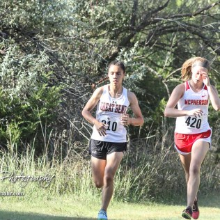 Great Bend's Mayra Ramirez (#210) runs slightly ahead of Kassidy Beam (#420) of McPherson. The Great Bend Cross Country Invitational was held at Lake Barton near Great Bend, Kansas on August 30, 2018. (Photo: Joey Bahr, www.joeybahr.com)