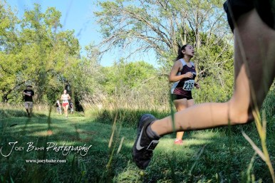 Cristina Leos (#235) of Hays runs in a shaded part of the course. The Great Bend Cross Country Invitational was held at Lake Barton near Great Bend, Kansas on August 30, 2018. (Photo: Joey Bahr, www.joeybahr.com)