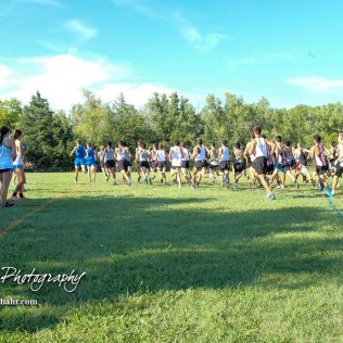 The boys varsity competitors run towards the woods at the start of the race. The Great Bend Cross Country Invitational was held at Lake Barton near Great Bend, Kansas on August 30, 2018. (Photo: Joey Bahr, www.joeybahr.com)