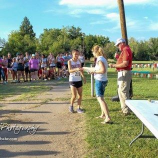 Great Bend's Mayra Ramirez accepts the first place medal for the girls varsity race. The Great Bend Cross Country Invitational was held at Lake Barton near Great Bend, Kansas on August 30, 2018. (Photo: Joey Bahr, www.joeybahr.com)