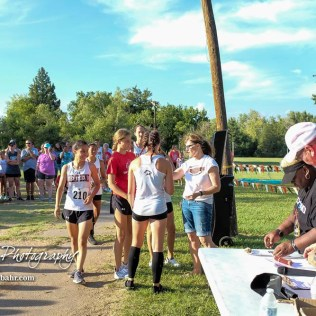 The Great Bend varsity girls team approaches to receive their first place team medals. The Great Bend Cross Country Invitational was held at Lake Barton near Great Bend, Kansas on August 30, 2018. (Photo: Joey Bahr, www.joeybahr.com)