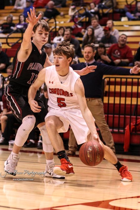 Hoisington Cardinal #5 Ryan Wyodziak drives around Plainville Cardinal #11 Anders Dewey in the first quarter. The Hoisington Cardinals defeated the Plainville Cardinals by a score of 70 to 53 at the Hoisington Activity Center in Hoisington, Kansas on February 5, 2019. (Photo: Joey Bahr, www.joeybahr.com)