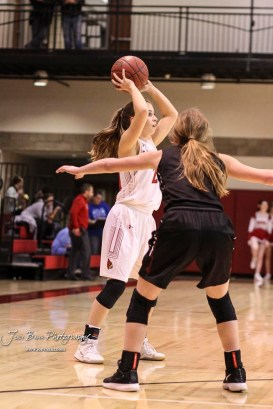 Hoisington Lady Cardinal #21 Suzanna Schneider looks for an open teammate to pass the ball to in the first quarter. The Plainville Lady Cardinals defeated the Hoisington Lady Cardinals by a score of 49 to 35 at the Hoisington Activity Center in Hoisington, Kansas on February 5, 2019. (Photo: Joey Bahr, www.joeybahr.com)