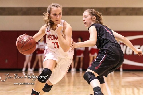 Hoisington Lady Cardinal #21 Suzanna Schneider drives to the basket past Plainville Lady Cardinal #4 Brooke Nuss in the first quarter. The Plainville Lady Cardinals defeated the Hoisington Lady Cardinals by a score of 49 to 35 at the Hoisington Activity Center in Hoisington, Kansas on February 5, 2019. (Photo: Joey Bahr, www.joeybahr.com)