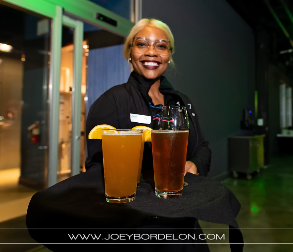Friendly Top Golf server offering beverages to guests