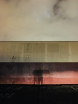 Mysterious shadow of a person at night against a painted urban wall