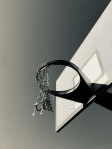 A playground basketball hoop with a ripped net isolated against the sky