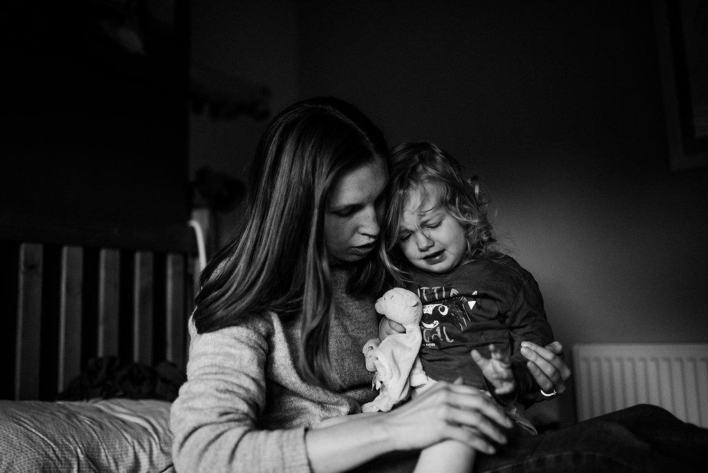 Mother rubbing little girl's hurt knee
