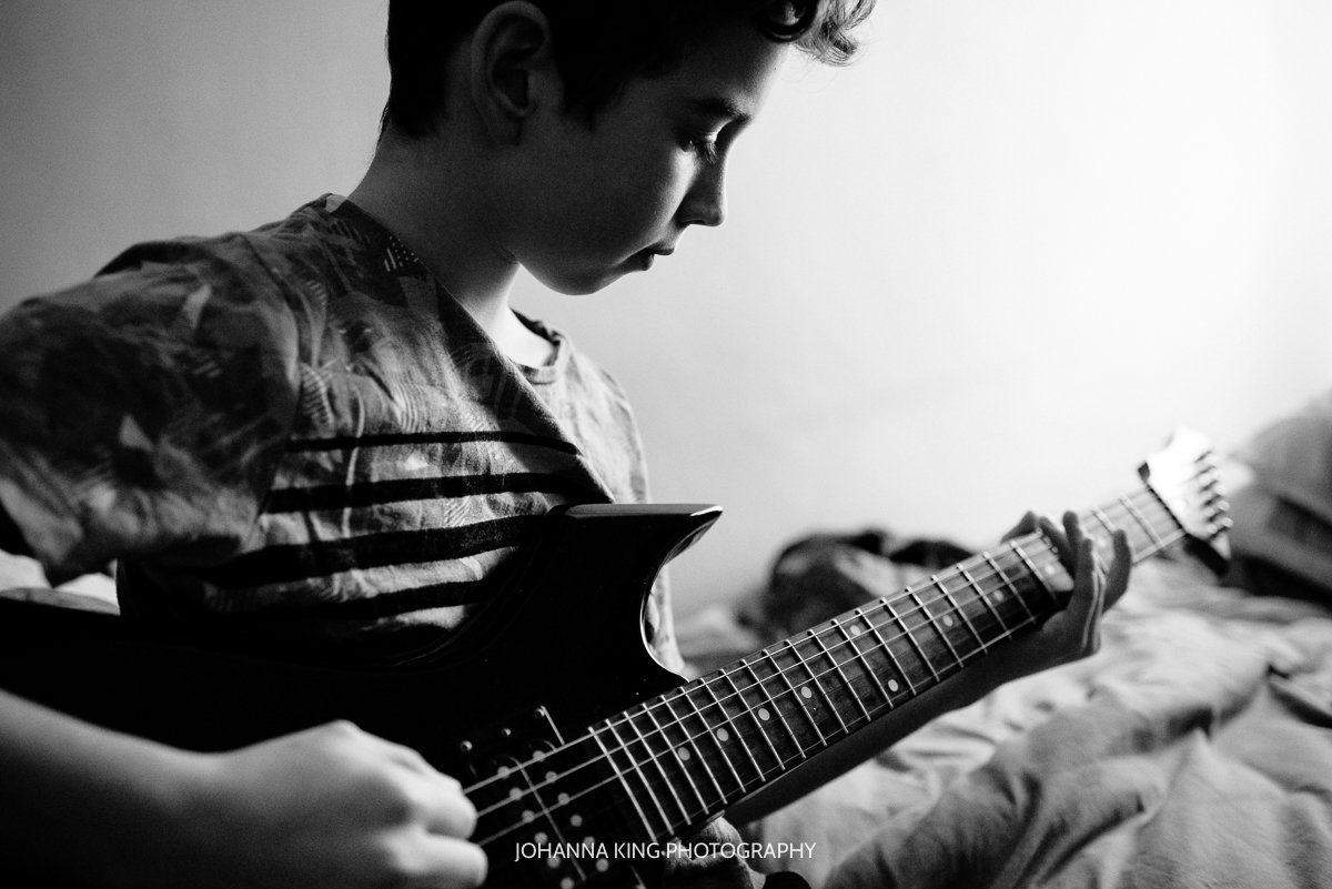 Boy playing guitar in his bedroom