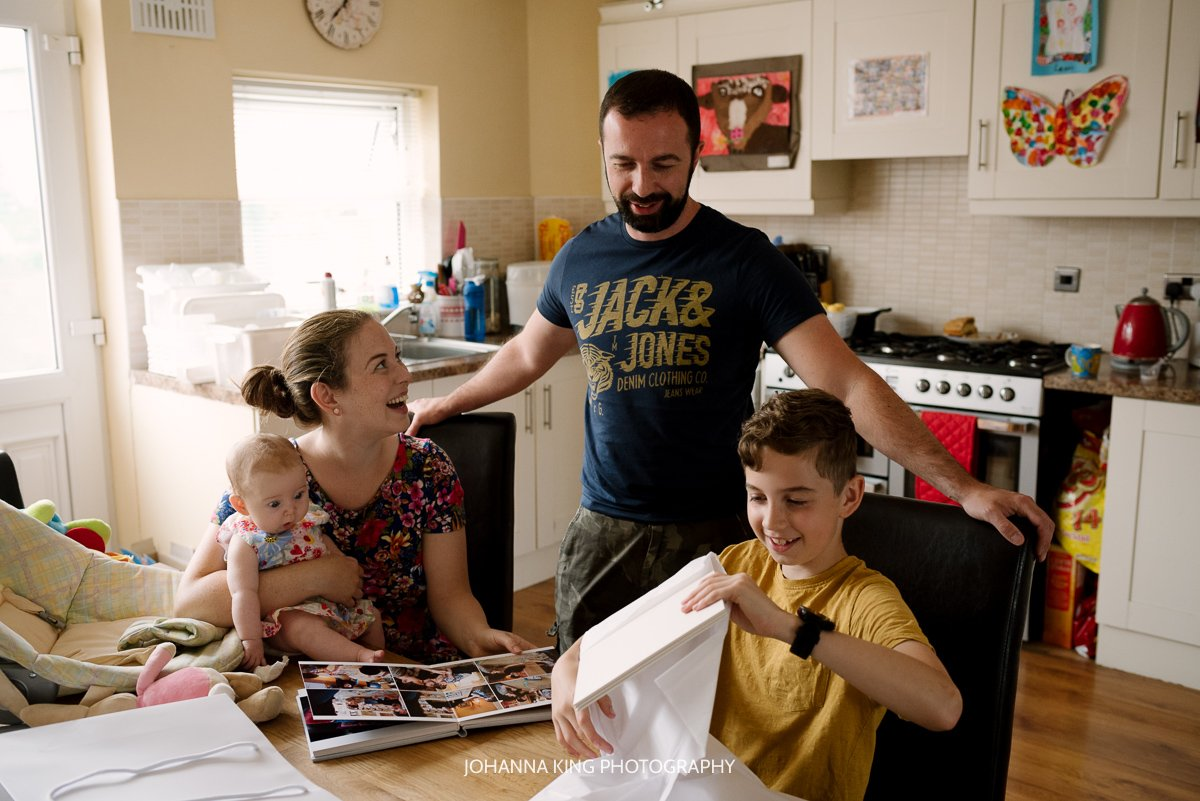 Family opening their print order in their kitchen and laughing