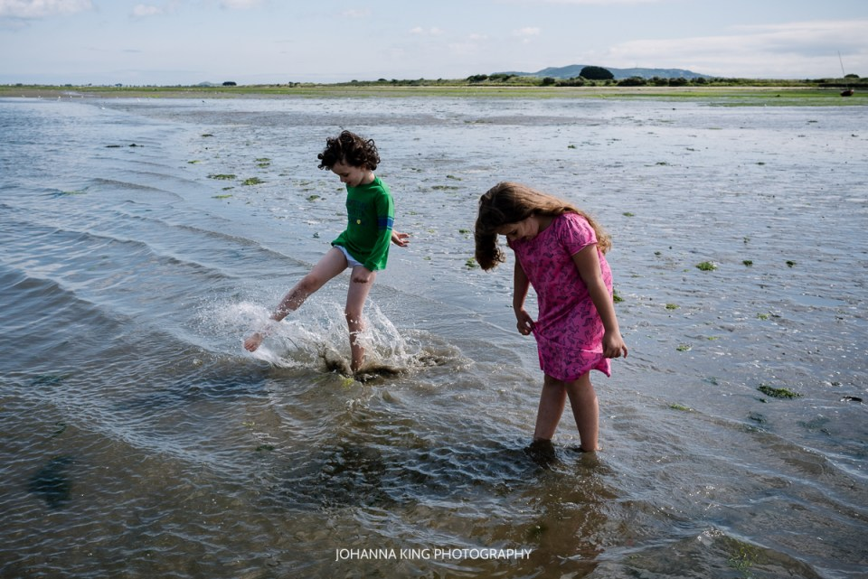 Siblings getting their PJs wet while playing with water on the beach in Dublin