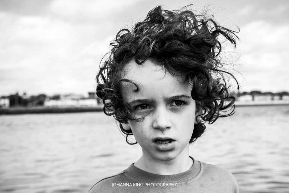 Black and white portrait of a son and his curly hair flying in the wind.