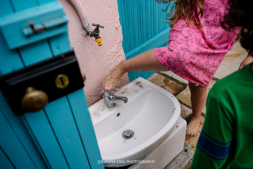 Girl washing her feet off the tap in the garden, above a sink.