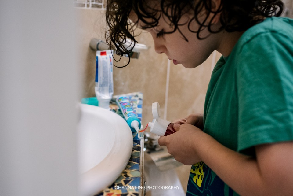 Son putting toothpaste on his tooth brush with great concentration.