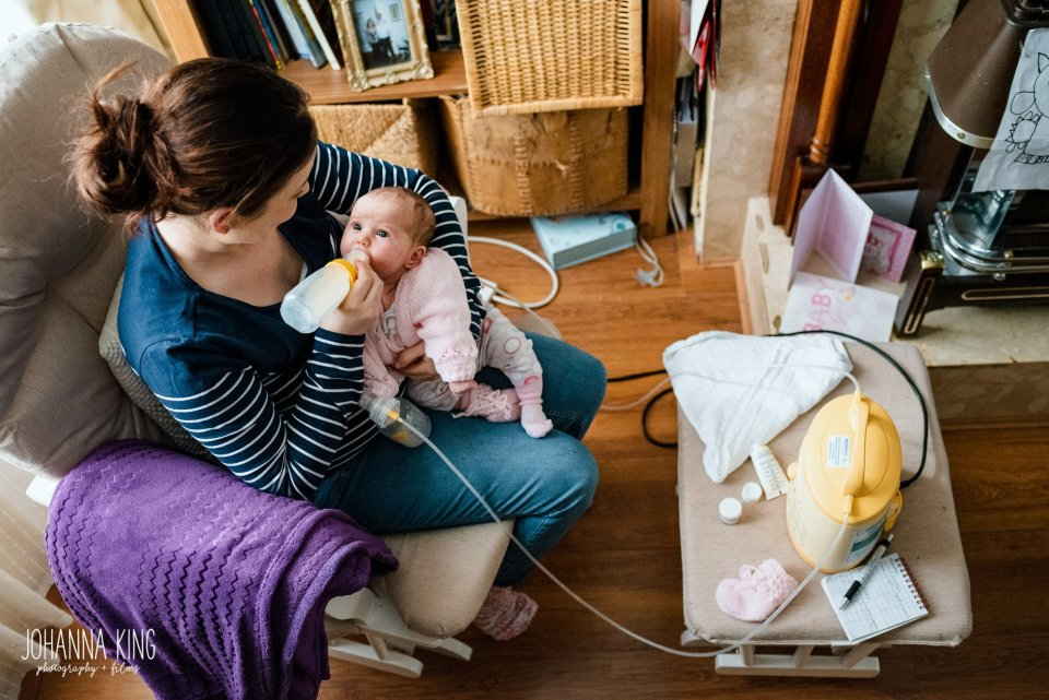 Mother giving a bottle to her newborn baby while expressing milk at the same time at home - Documentary Newborn Photography Example