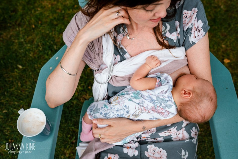 Mother breastfeeding her baby girl outside in her garden while drinking a cup of coffee - Documentary Newborn Photography Example
