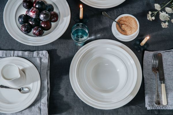 Table set with luxury porcelain dinnerware on dark linen tablecloth